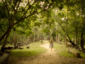 Young woman in dress walking barefoot on a mysterious path into an enchanted forest.